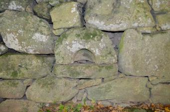 Antiga pía reutilizada no muro dunha vivenda