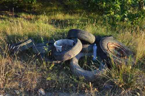 Rodas e outros residuos a carón do verquido de pezas de coche, en Fonte das Pulgas