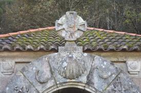 Detalle do arco na porta de acceso, coa cuncha e a cruz na parte central