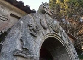 Detalle do arco na porta de acceso: barco, áncora, peixe, cuncha, gaivota